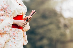 Asian girl wearing a kimono stand holding fan on a green grass